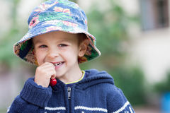 Adorable boy, eating sweet cherries and smiling Stock Photo