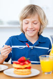 Adorable boy eating waffles with strawberries. In the kitchen Royalty Free Stock Photos