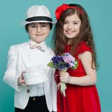 Adorable boy and girl, wear elegant suit and red dress, posing in studio, isolated on turquoise background. royalty free stock photography
