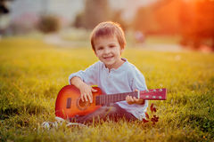 Adorable boy with guitar, sitting on the grass Stock Photo
