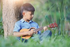 Adorable boy with guitar sitting on the grass on sunset, Musical concept with little boy playing ukulele at sunny park royalty free stock photos