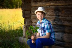 Adorable boy in hat smelling of lilac a bouquet of flowers in the countryside. royalty free stock photo