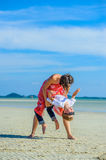 Adorable boy having fun with his mom on the tropical beach. White t-shirt, dark trousers and sunglasses. Barefoot on white sand. stock images