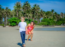 Adorable boy having fun with his mom on the tropical beach. White t-shirt, dark trousers and sunglasses. Barefoot on white sand. Adorable boy having fun with Royalty Free Stock Photography