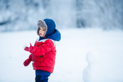 Adorable boy having fun with snow. On winter day stock photo