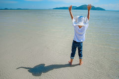 Adorable boy having fun on the tropical beach. White t-shirt, dark trousers and sunglasses. Barefoot on white sand. Adorable boy having fun on the tropical Royalty Free Stock Image