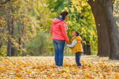 Adorable boy with his mother in autumn park Stock Photos