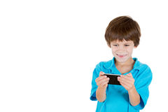Adorable boy holding cell phone in hands and happy by what he sees Royalty Free Stock Images