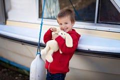 Adorable boy, holding his teddy bear, smiling Stock Photo
