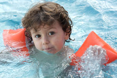 Adorable boy learning to swim Stock Photos