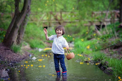 Adorable boy with little basket, full of flowers on a little pon Stock Photography