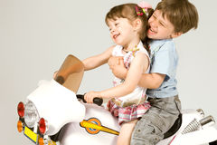 Adorable boy and little girl sitting on toy bike Stock Image