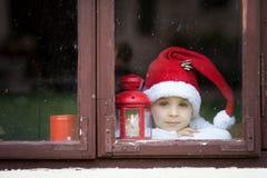 Adorable boy, looking through window, waiting for Santa Stock Photos