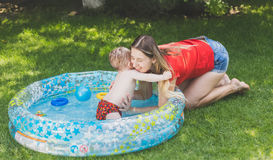 Adorable boy in outdoor swimming pool playing with mother Stock Photos