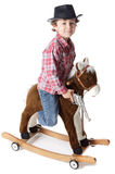 Adorable boy playing cowboys with a wood horse Royalty Free Stock Photo