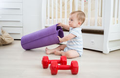 Adorable boy playing with dumbbells and fitness mat at living ro Stock Photos