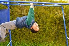 Playground boy. Boy at playground hanging upside down royalty free stock image