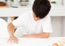 Adorable boy preparing a dough alone Stock Image