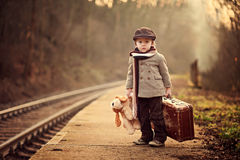 Adorable boy on a railway station, waiting for the train. With suitcase and teddy bear stock photos
