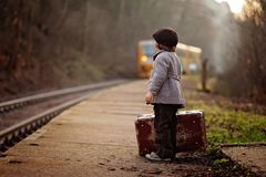 Adorable boy on a railway station, waiting for the train with suitcase and teddy bear royalty free stock images