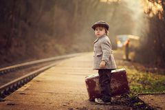 Adorable boy on a railway station, waiting for the train with suitcase and teddy bear royalty free stock image
