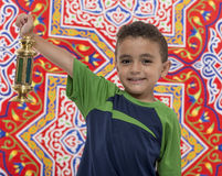 Adorable Boy with Ramadan Lantern. Adorable Boy with Vintage Lantern over Festive Ramadan Fabric Royalty Free Stock Images
