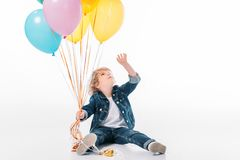 Adorable boy reaching bundle of balloons with hand. Isolated on white stock image