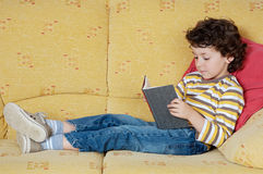 Adorable boy reading. Adorable happy boy reading in the armchair of your house Royalty Free Stock Photo