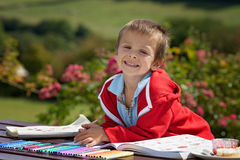 Adorable boy in red sweater, drawing a painting in a book, in th Stock Images
