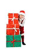 Adorable boy in santa clothes peeks out behind Christmas big gift boxs. Isolated white background. Royalty Free Stock Photography