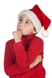 Adorable boy with santa hat thinking Stock Images