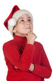 Adorable boy with santa hat thinking Royalty Free Stock Photography