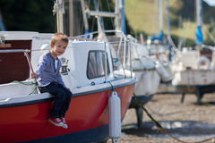 Adorable boy, sitting on a boat on the harbor Royalty Free Stock Images