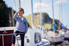 Adorable boy, sitting on a boat on the harbor, low tide Royalty Free Stock Photo