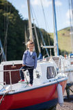 Adorable boy, sitting on a boat on the harbor, low tide Stock Photography