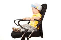 Adorable boy sitting on a chair Royalty Free Stock Image