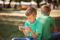 Adorable boy sitting on the grass in the park and playing with smartphone. Child learning how to use smartphone royalty free stock image