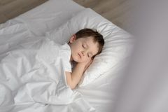 Adorable boy sleeping in bed, happy bedtime in white bedroom Royalty Free Stock Image