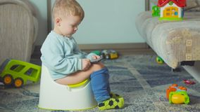 Adorable boy with a smartphone during potty training on the room. stock video