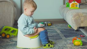 Adorable boy with a smartphone during potty training on the room. stock video footage
