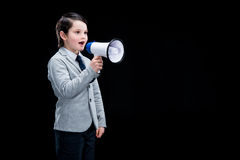 Adorable boy standing with megaphone and yelling Royalty Free Stock Photo