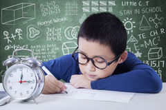 Adorable boy studying with alarm clock Stock Photography