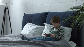 Adorable boy using smart phone playing on line. Concentrated cute preschool boy with mobile phone playing interesting on line games while sitting on the bed in stock video footage
