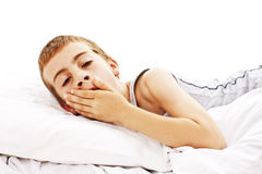 Adorable boy is yawning in a bed Stock Photos