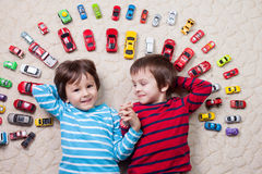 Adorable boys, lying on the ground, toy cars around them , looki Stock Images