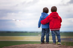 Adorable boys in read and blue jackets, stanging on a hill, watc Royalty Free Stock Photo