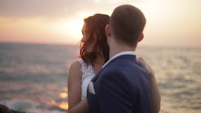Adorable bride and handsome groom are tenderly hugging near the sea at the background of the bright colorful sunset. stock video