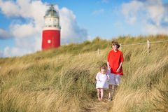 Adorable brother and sister on beach next to lighthouse Stock Photos