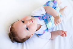 Adorable brunette baby girl in purple overalls Stock Image