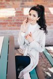 Adorable brunette woman in white coat and black trousers sitting. Indoors over brick wall talking on cellphone with her man discussing their date and royalty free stock images
